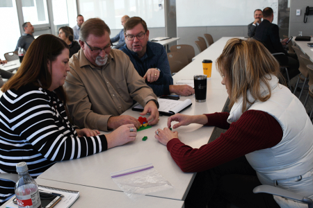 Corporate staff at Alvine Engineering work on team building skills with Legos.
