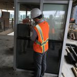 Brandon Rich comparing windows at the 1201 Cass construction site