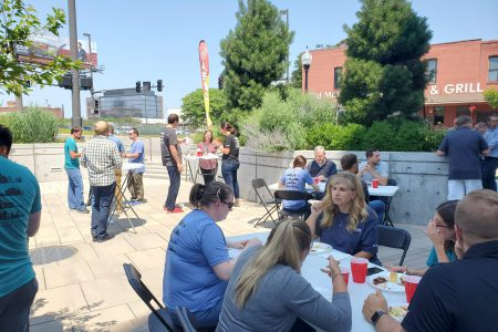 Alvine Engineering staff eat lunch to celebrate the firm's 60th anniversary